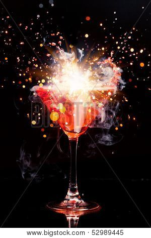 red cocktail with splash, sparkler and ice vapor