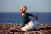 stock photo of stretching exercises  - Senior woman in stretching position by the sea at morning - JPG