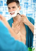 Young man shaving with a razor blade and shaving cream in bathroom