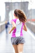 City runner - woman running on Brooklyn Bridge. Rear view backside close up of female athlete traini