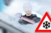 picture of scrape  - winter driving - Woman scraping ice from a windshield. Photo is has been taken from the inside of the car. - JPG