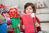 Portrait of boy sitting by stacked Christmas presents at home