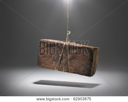 An old worn brick dangling from a string.
