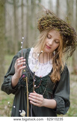Portrait Of A Girl In A Folk  Medieval Style With A Circlet Of Flowers Looking At The Willow Branch