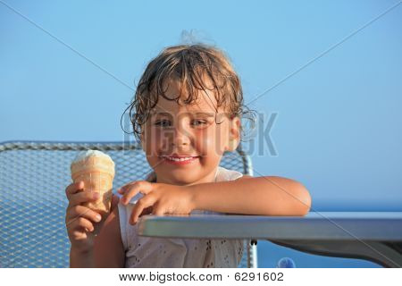 Smiling Little Girl Eats Ice-cream On Resort