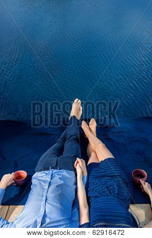 Couple Lying On Terrace Near Water