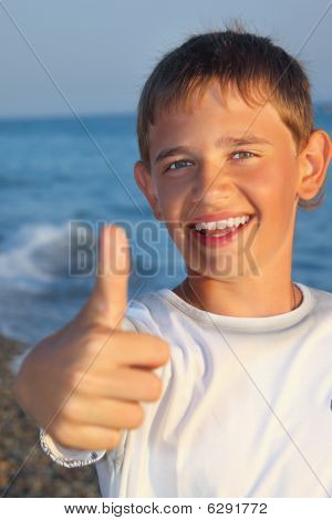 Smiling Teenager Boy Against Sea Shows Gesture ок