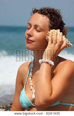 Beautiful Woman Has Leant Seashell Bowl To An Ear On Seacoast