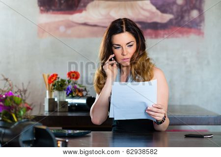 Young woman on the phone in a cafe or restaurant, she discusses some documents