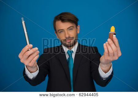 businessman holding e-cigarette and e-liquid on blue background