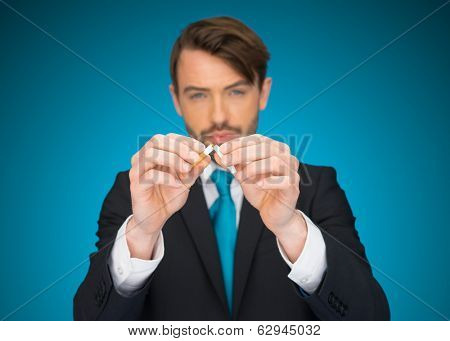 business holding a broken cigarette giving up smoking