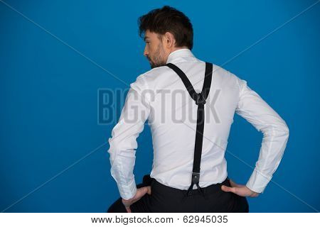 handsome man on blue wearing white shirt and braces from the back