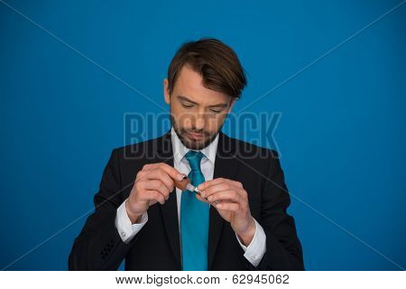 businessman topping up his e-cigarette with e-liquid on blue background