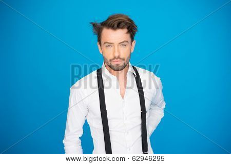 handsome man on blue wearing white shirt and braces on blue with crazy hair style