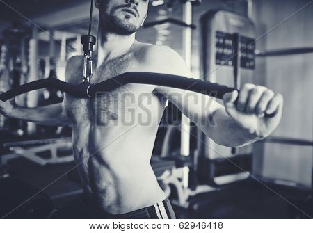 Young man stretching pectoral muscles on special sport equipment