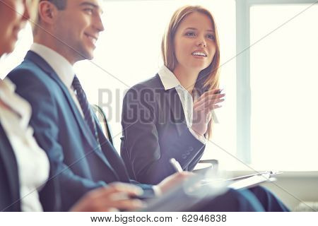 Smart businesswoman asking question at seminar with her colleagues near by