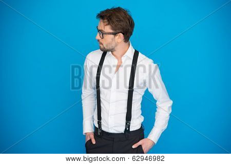 handsome man on blue wearing white shirt and braces on blue with glasses