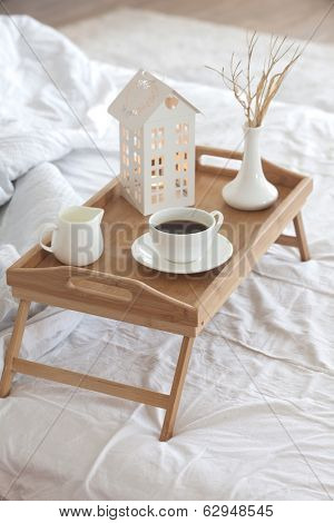 Wooden tray with coffee and interior decor on the bed with white linen