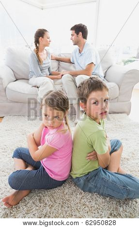 Pouting siblings sitting back to back while parents are arguing at home in the living room