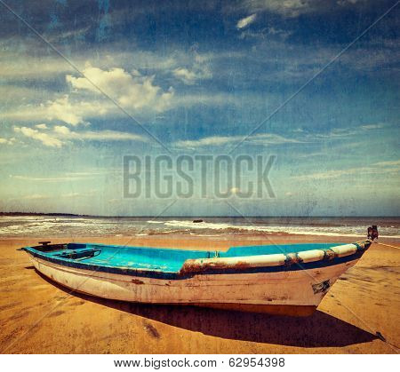 Vintage retro hipster style travel image of boat on a beach, India  with grunge texture overlaid