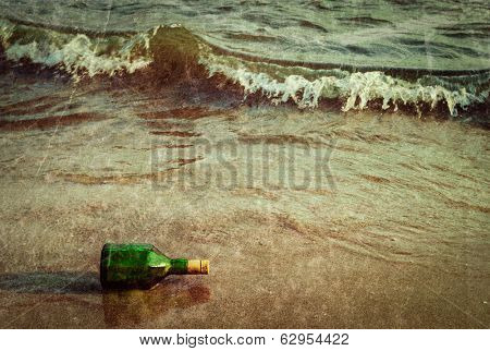 Vintage retro hipster style travel image of message bottle on beach sand in waves with grunge texture overlaid