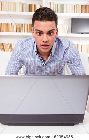 Concerned Man Looking At Computer Monitor Shocked