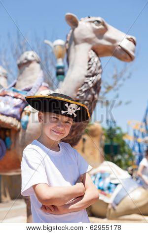 Boy in a pirate hat in amusement park.