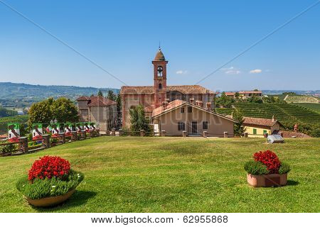 Green lawn in front of small rural church under blue sky in Piedmont, Northern Italy.