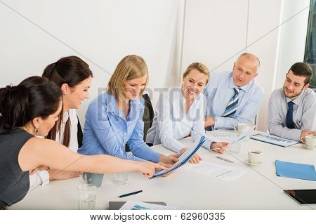Business Team sitting around meeting table discussing file