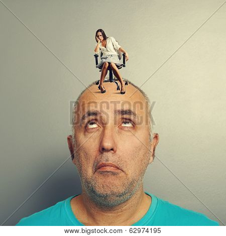 amazed man with small tired woman over grey background