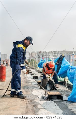 Workers make waterproofing of seams on the bridge