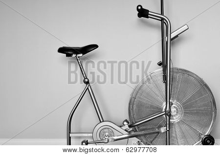 Detail closeup of stationary exercise bike with white wall