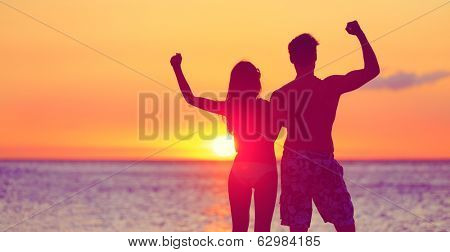 Happy fitness people on beach at sunset flexing showing muscles. Cheering winning couple expression joy and success together embracing. Man and woman on tropical beach.