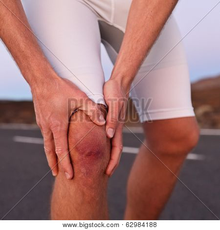Knee injury - athlete runner with sport injury. Male runner having knee problems during exercise outside.