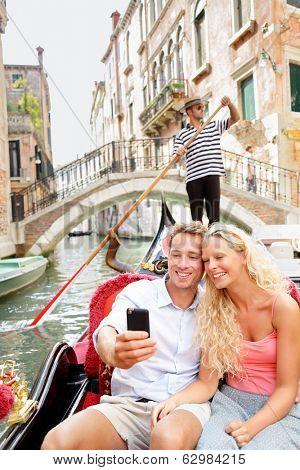 Travel couple in Venice on Gondole ride romance in boat happy together on travel vacation holidays. Romantic young beautiful couple taking self-portrait sailing in venetian canal in gondola. Italy.
