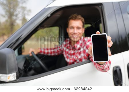 Smart phone man in car driving showing smartphone display smiling happy. Male driver using apps showing blank empty screen sitting in drivers seat. Focus on mobile cell phone.