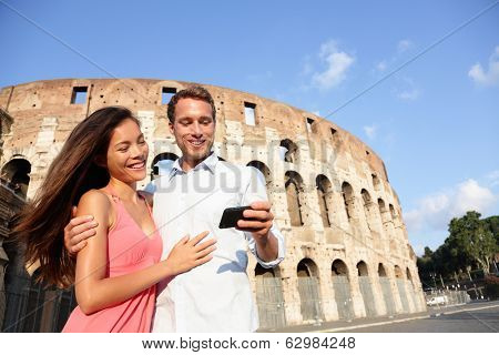 Couple in Rome by Colosseum using smart phone looking at pictures or using travel app in Italy. Happy lovers on honeymoon sightseeing Coliseum. Love and travel concept with multiracial couple.