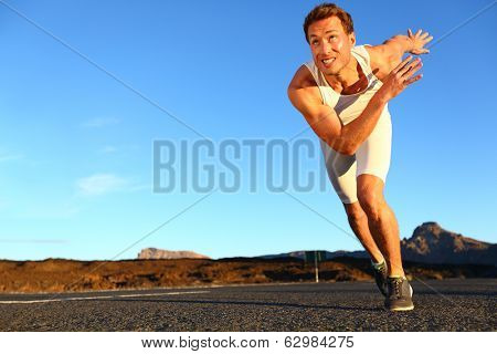 Sprinting man running. Runner sprinter at fast speed training towards goals and success. Fit muscular male athlete in workout outdoors on road.
