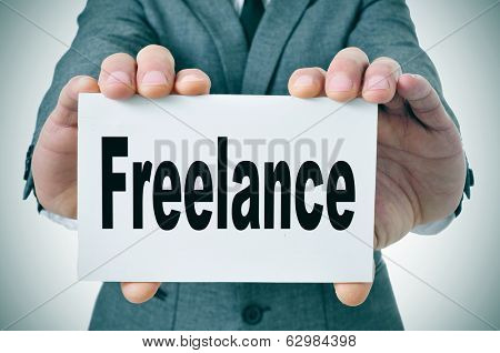 businessman showing a signboard with the word freelance written in it