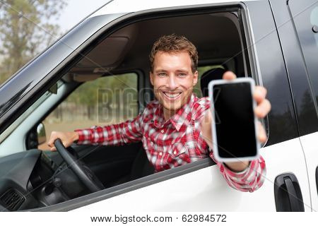 Smartphone man in car driving showing smart phone display smiling happy. Male driver using app showing blank empty screen sitting in drivers seat. Focus on model.