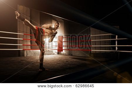 Young man kickboxing in the Arena
