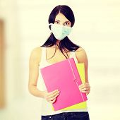 Caucasian student woman with mask on her face. She is defending her self from viruses.