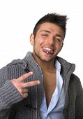 foto of piercings  - Attractive young man smiling with tongue piercing doing victory sign with two fingers - JPG