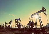 working oil pumps silhouette in row against sun - vintage retro style