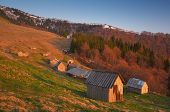 stock photo of hamlet  - Wooden houses for shepherds and sheep barns in the mountains - JPG