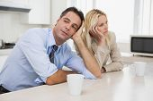 stock photo of not talking  - Unhappy business couple not talking after an argument in the kitchen at home - JPG