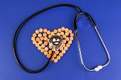 Heart of pills and stethoscope on blue background