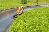 image of luge  - Young woman enjoying summer sledge ride - JPG