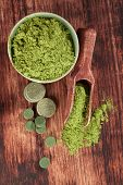 image of chlorella  - Detox. Chlorella spirulina and wheatgrass ground and pills with wooden spoon on brown wooden background top view. Alternative medicine.