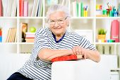Smiling senior woman sitting at home on a sofa and reading a book.